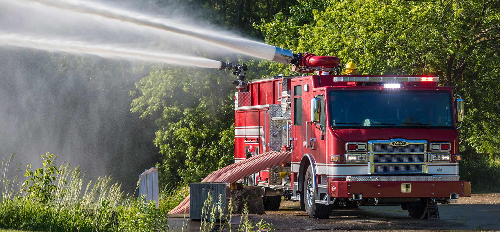 A red industrial fire truck is pumping water in a green wooded setting.