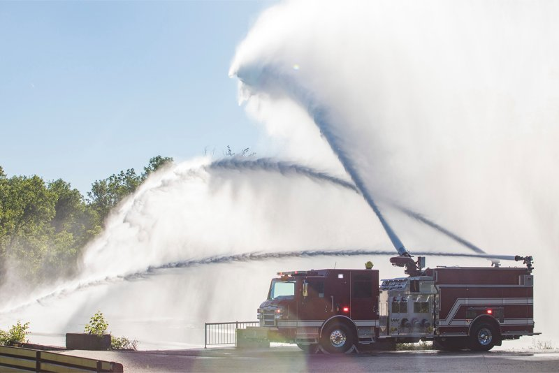 An industrial pumper truck is spraying water from three large nozzles in an outdoor setting.