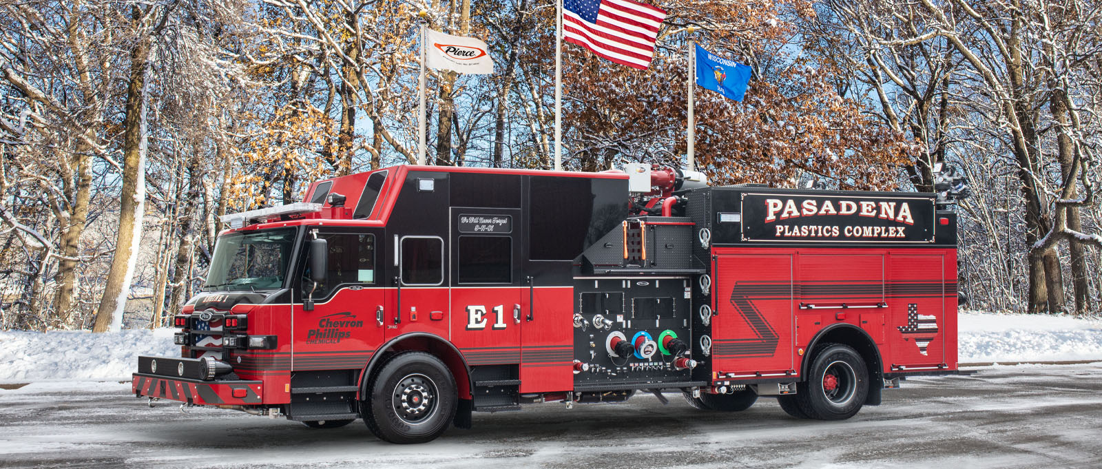 The Pasadena industrial pumper truck is pictured in winter in front of flags in the Pierce Manufacturing parking lot.