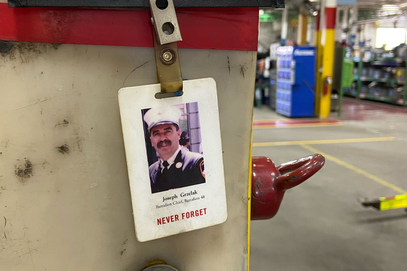 A 9/11 Memorial Stair Climb badge showing a fallen firefighter hangs at a desk workstation at Pierce Manufacturing.