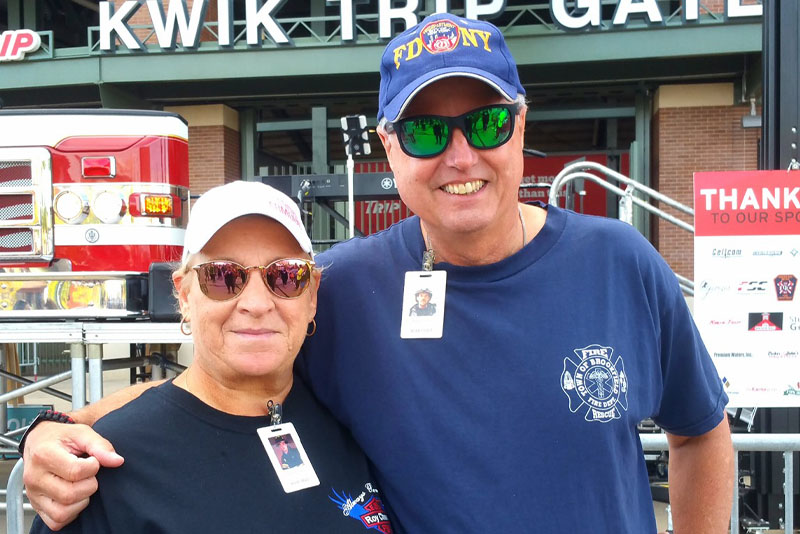 A woman and man stand in front of the Kwik Trip Gate at Lambeau Field after the 9/11 Memorial Stair Climb.