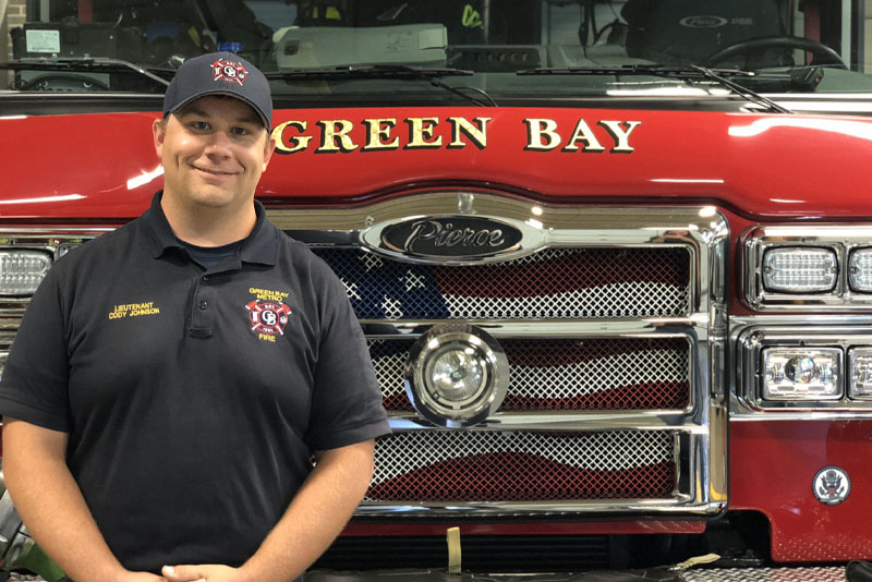 A Green Bay Metro Fire Department fire fighter stands in front of a red fire truck.