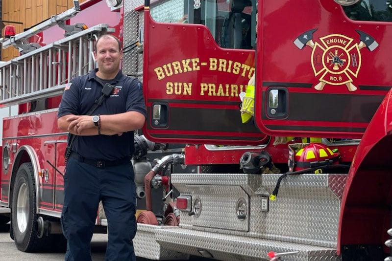 A Sun Prairie firefighter fire fighter stands outside a red fire truck outdoors.