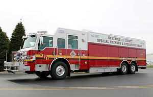 Side and front view of a Pierce Manufacturing Combination Rescue Truck. Showing compartments and storage area along side the apparatus.