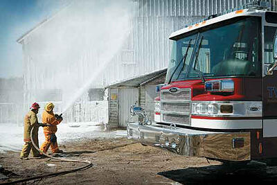Firefighters holding hose while putting out a fire next to a Pierce Manufacturing fire truck that has corrosion and chemical resistance properties.