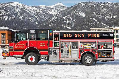 Pierce fire apparatus with all compartments open, parked in the snow with snowy mountainous surroundings.