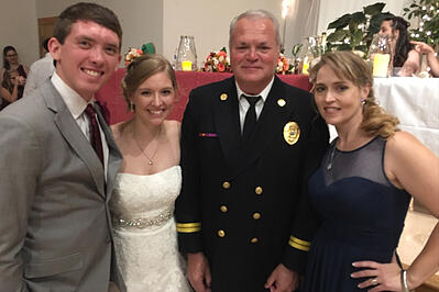 Spartan Fire and Emergency Apparatus sales representative, Alan Axson, poses for a photo with Tara, her husband Mitchell, and mother, Melody.