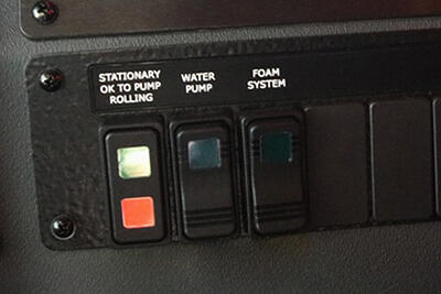 PUC control system displaying button options for front flood, DS, Rear, and PS Scene as well as the button to flip on for pump rollong, the water pump, and the foam system.