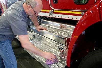 Pierce employee polishing a fire truck step using an instant detailer.