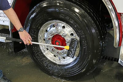 A fire department is washing its fire truck going from panel by panel, top to bottom, ending with a thorough scrubbing of the fire truck wheel.