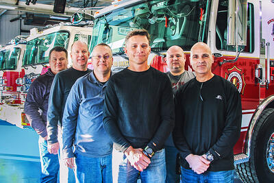 Members of the customer experience team pictures on the blue floor in front of completed fire apparatus.