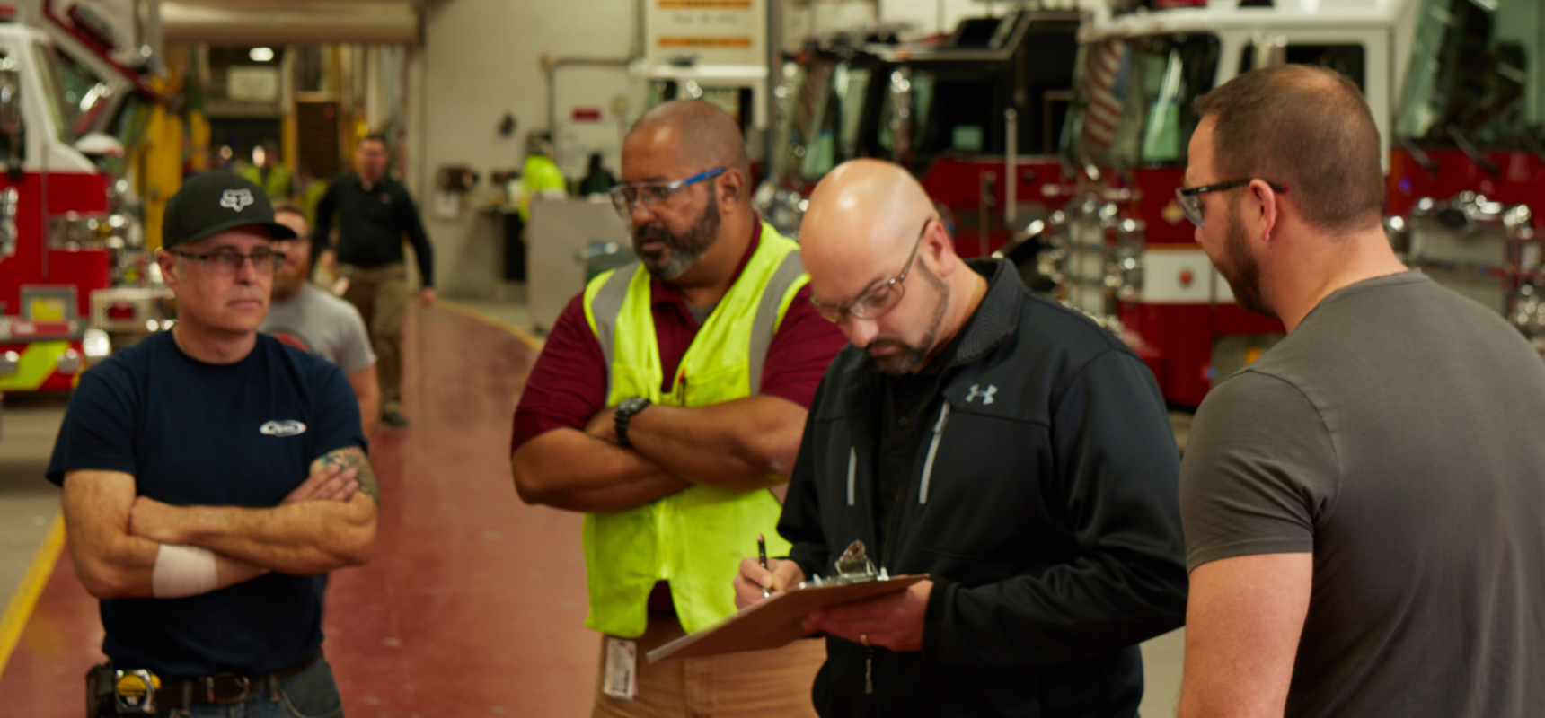 Fire department and Pierce representatives review items on a clipboard with fire trucks in the facility background.