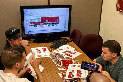 Pierce customers and team members sit around a table and computer monitor to review fire truck renderings.