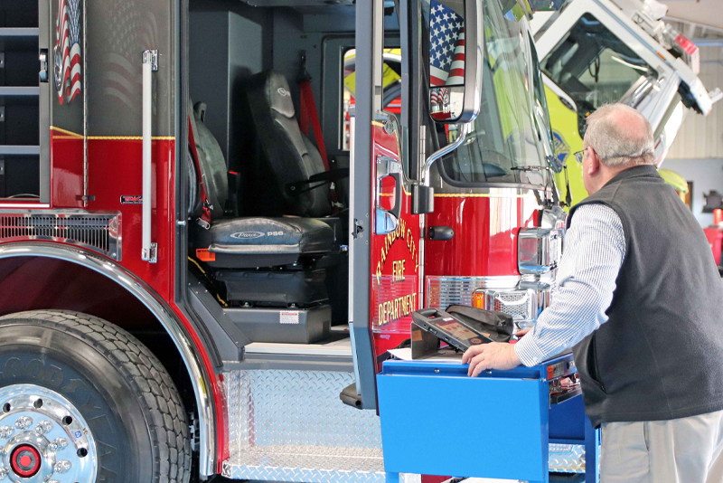 A Pierce employee is performing a final product evaluation by inspecting this fire truck with great detail using a documentation system on his tablet.