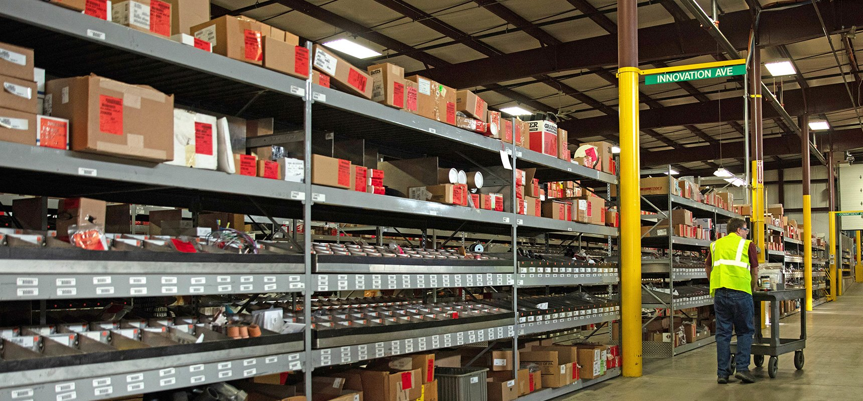 Pierce product support supply warehouse with shelves stocked full of boxes, showing an employee pushing a cart of parts down an aisle.