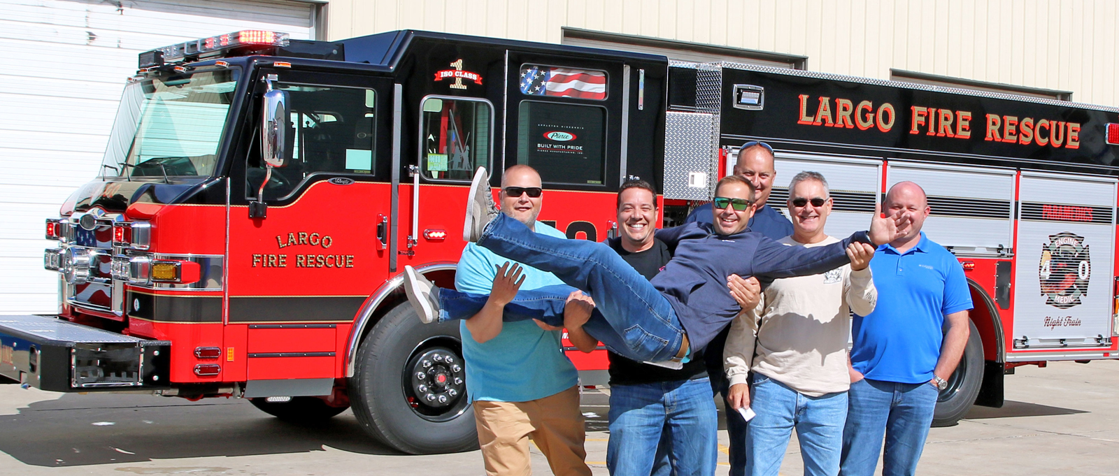 A group of fire fighters joke around with one throw in the air in front of their new fire truck at Pierce's facility.