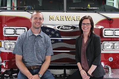 Two Pierce former interns, now full-time employees stand in front of a Pierce fire truck. Zach on left and Sheena on the right.