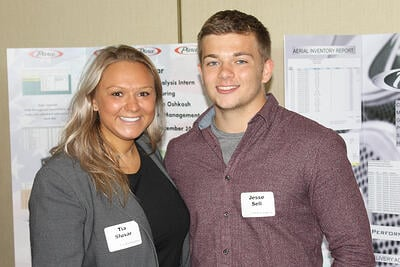 Two Pierce interns standing in front of their projects from the Pierce Intern Expo