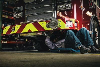 A Pierce Master Technician works under the fire truck cab
