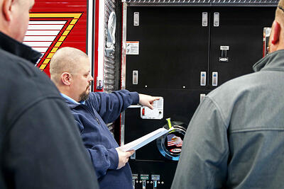 Pierce employee shows the quality of Pierce's fire truck by inspecting the fire truck with the customer.