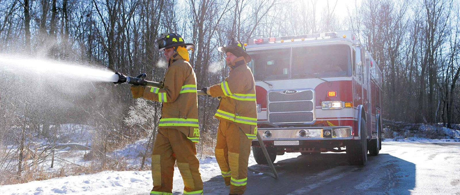 Firefighters using the pump and roll feature on the PIC apparatus. Carrying a fire hose and spraying water out in winter conditions