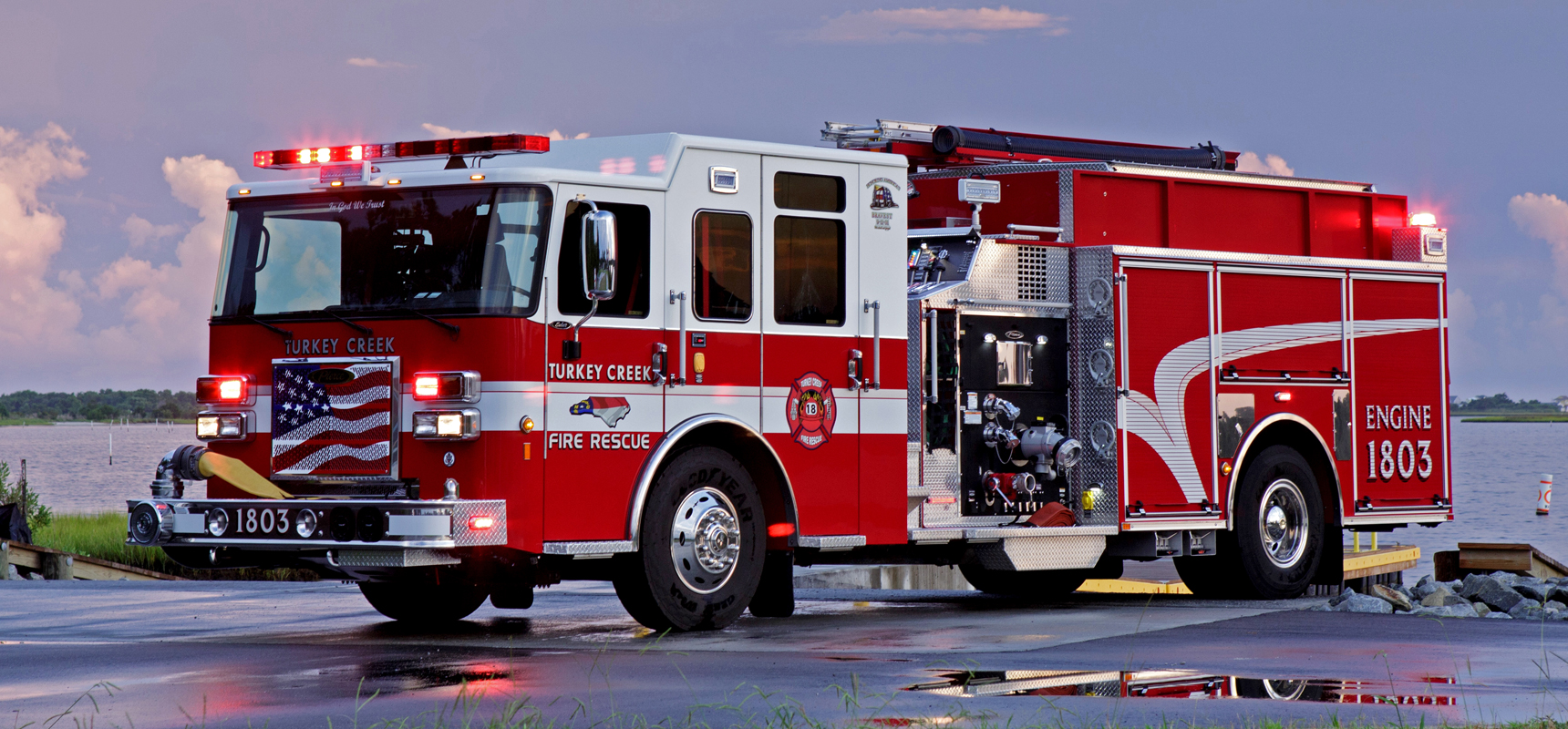 A Pierce Manufacturing Rescue Pumper from Turkey Creek shown with the storage doors open and emergency lighting displayed at dusk