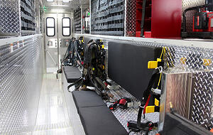 Interior view of a Pierce Manufacturing Walk-In Rescue Truck. Seating is shown as a bench along the side of the interior for first responders to sit