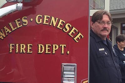 A firefighter with the Wales-Genesee Fire Department stands next to a fire apparatus.