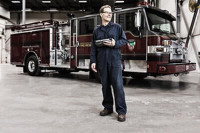 Fire apparatus customizations start with experienced team members who understand every aspect of fire apparatus. Pierce employee shown standing in front of fire apparatus with controls in hand