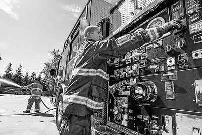 A firefighter manages the controls of a fire apparatus pump panel.