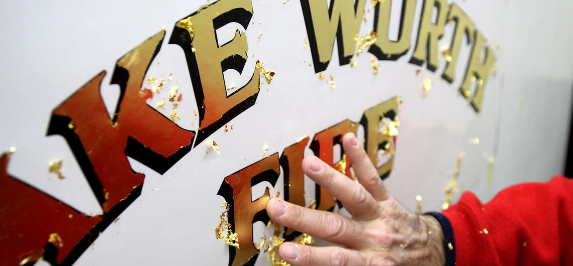 A hand is shown brushing over gold leaf lettering on a fire truck during the graphic application process.