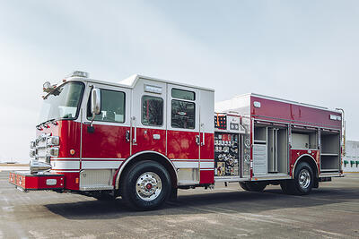 A fully equipped heavy-duty rescue pumper sits on a black tarmac.