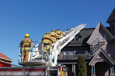 Firefighters climb an extended aerial device over a residence in a neighborhood.