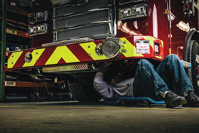 A mechanic performs a routine inspection of fire truck undercarriage, which can help to reduce surface rust and corrosion.