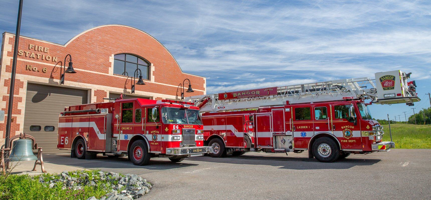 Two red and white fire trucks are parked outside their fire department bays with a bright blue sky in the background.