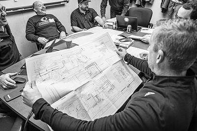 pierce-firetruck-dealersMembers of a fire department sit around a conference table with a fire apparatus dealer reviewing firetruck blueprints.