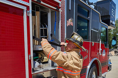 A firefighter at an emergency scene opens a compartment roll-up door to access equipment inside.
