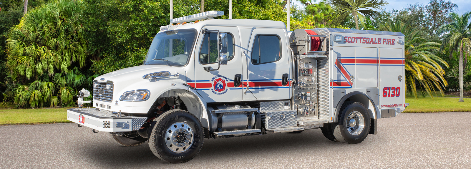 A white type 3 fire truck is parked showing the driver's side detail with trees in the background.