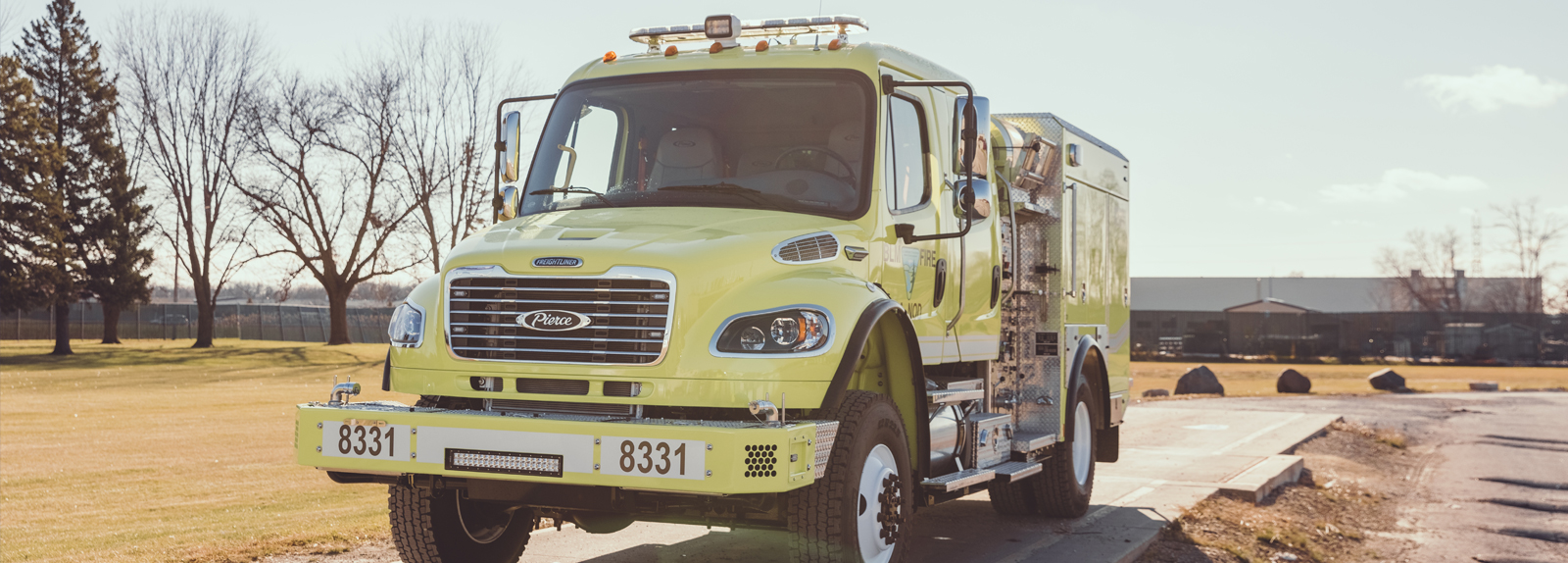 A yellow type 4 fire truck is parked facing forward showing the front end in a rural setting.