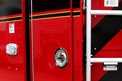 : A rescue pumper fire truck is positioned outdoors with hinged doors open to show the compartment interiors.