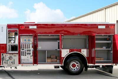 The body compartments of a red rescue pumper are opened to show the pump panel and impressive storage capabilities.