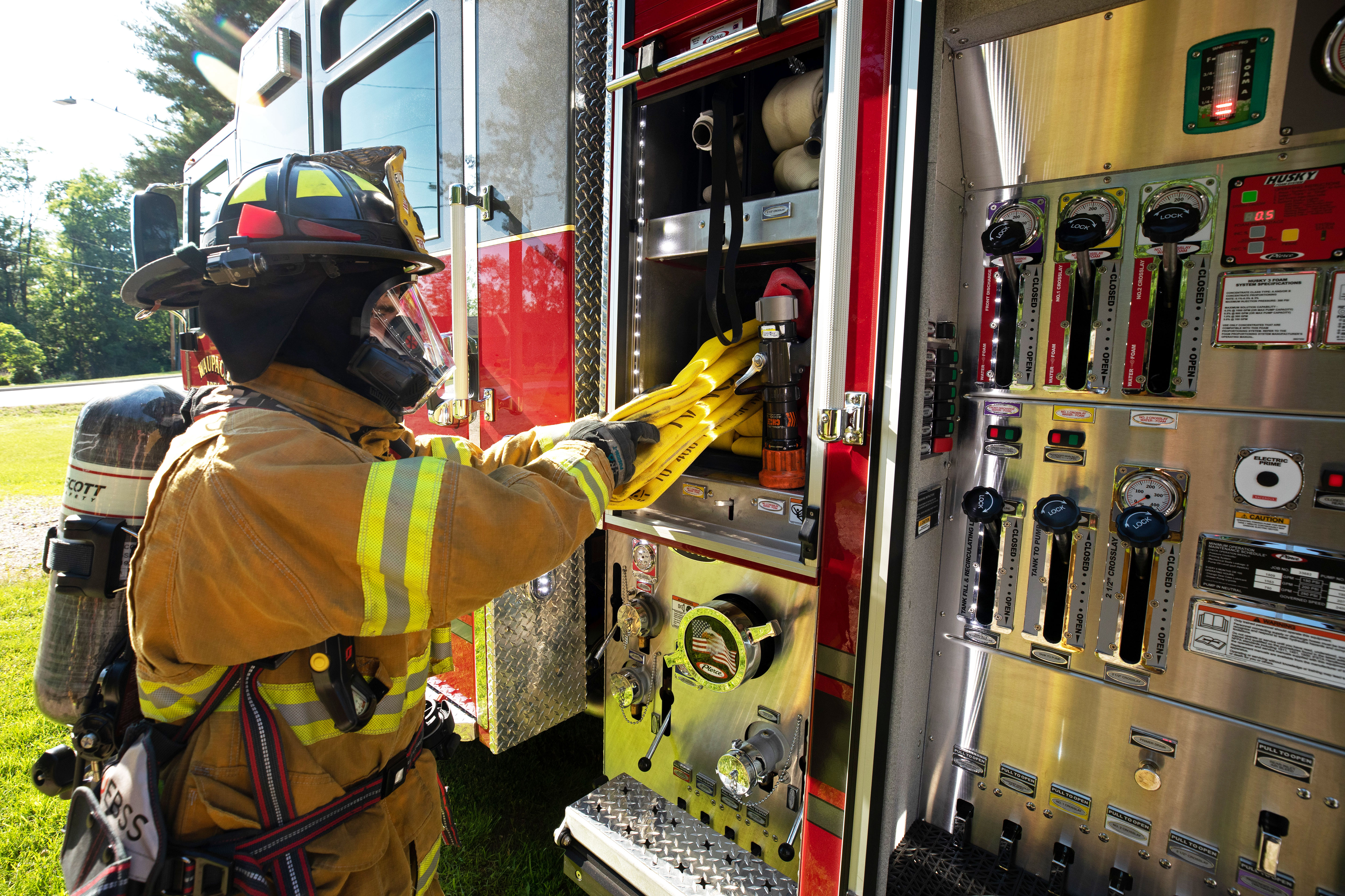 Firefighter Using Hose with PUC Pumper Fire Truck