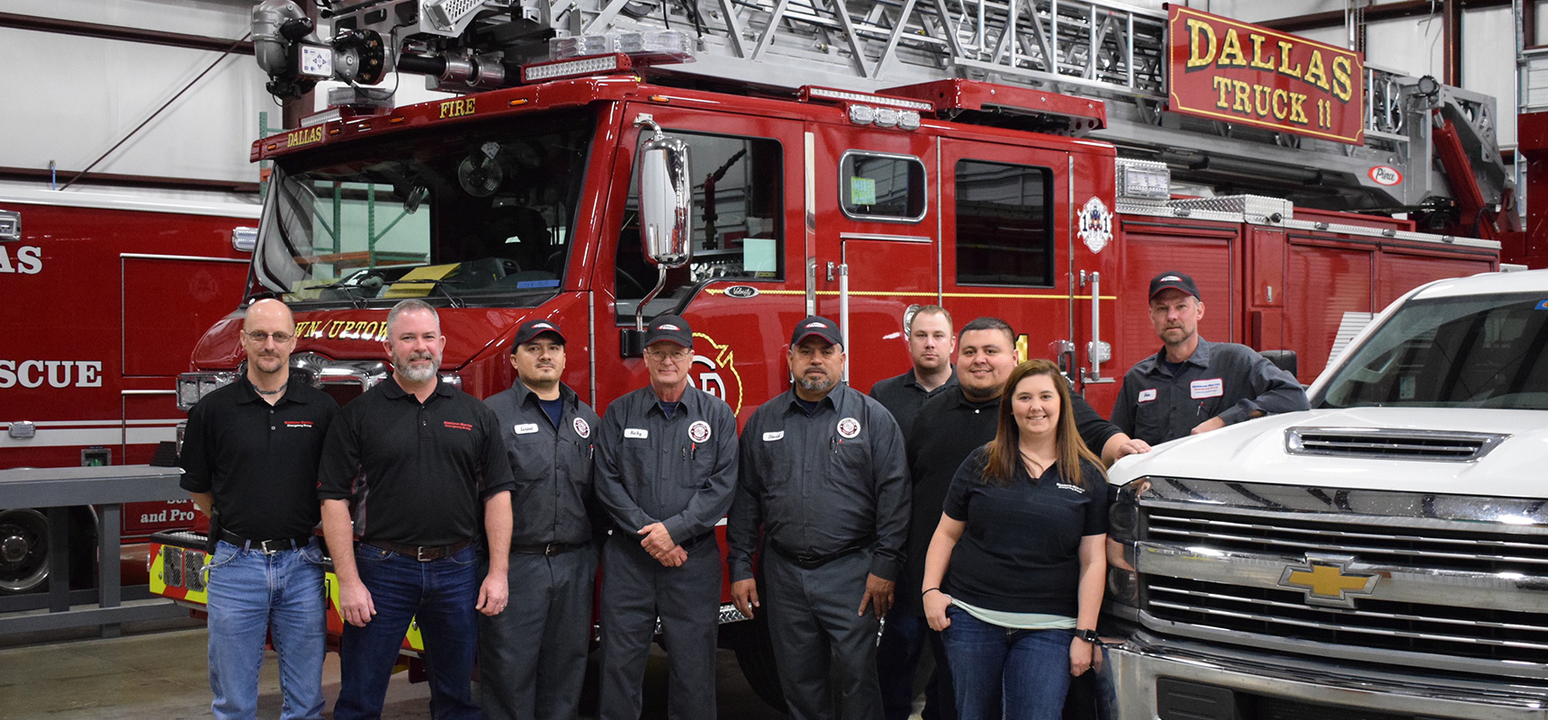 Siddons-Martin Emergency Group employees stand in front of a fire truck at one of the companies three new service centers.