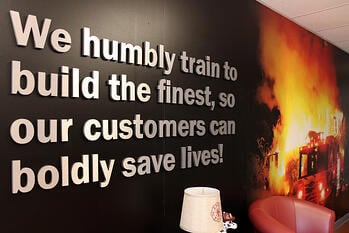 """Wall in the Pierce Training Center stating """"We humbly train to build the finest, so our customers can boldly save lives!"""""""